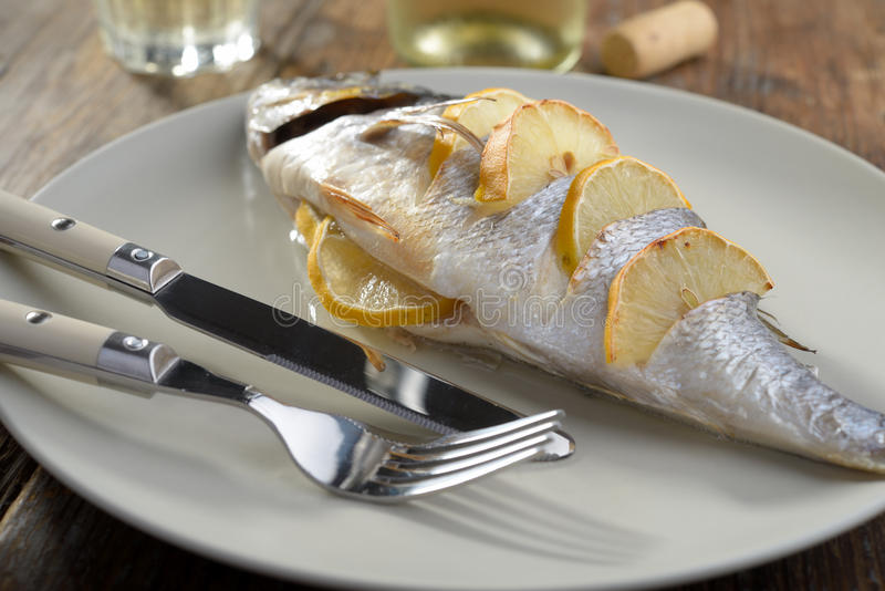 Baked sea bream. Baked gilt-head sea bream with lemon slices royalty free stock image