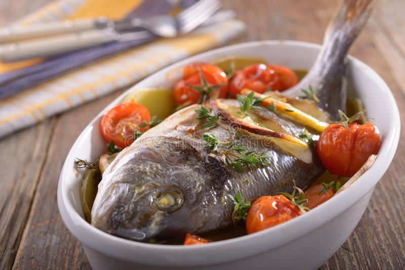 Baked sea bream. With vegetables in a baking dish stock images