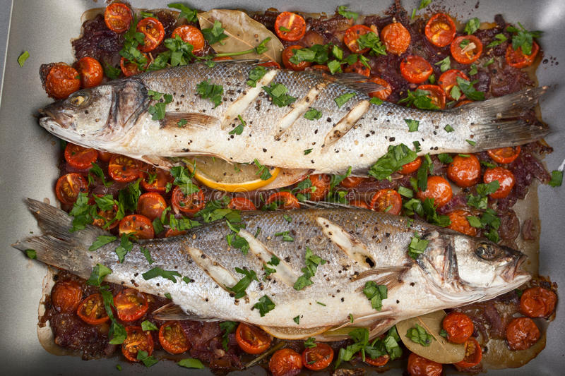 Baked Seabass Fish. Seabass Fish Baked with Vegetables, Cherry Tomatoes, Onions, Herbs and Lemon on a Dish stock images