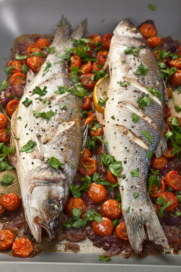 Baked Seabass Fish. Seabass Fish Baked with Vegetables, Cherry Tomatoes, Onions, Herbs and Lemon on a Dish stock image