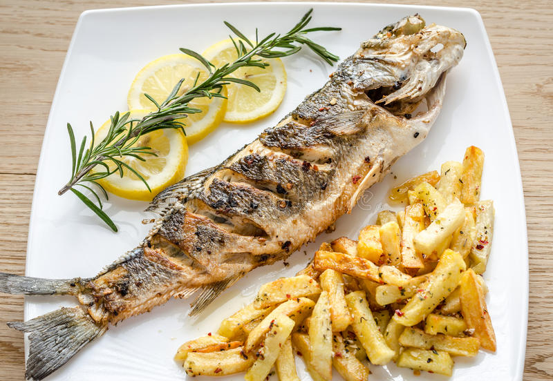 Baked seabass with fried potatoes. On the plate stock image