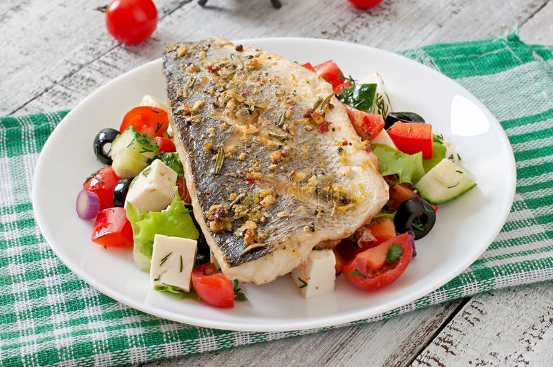 Baked seabass with Greek salad. On plate royalty free stock photos