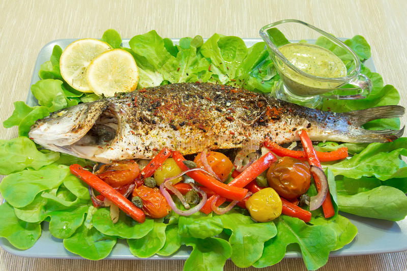 The baked seabass with vegetables. With sauce royalty free stock photos