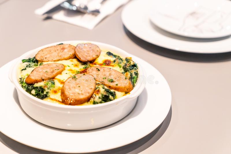 baked spinach with cheese and sausage stock image