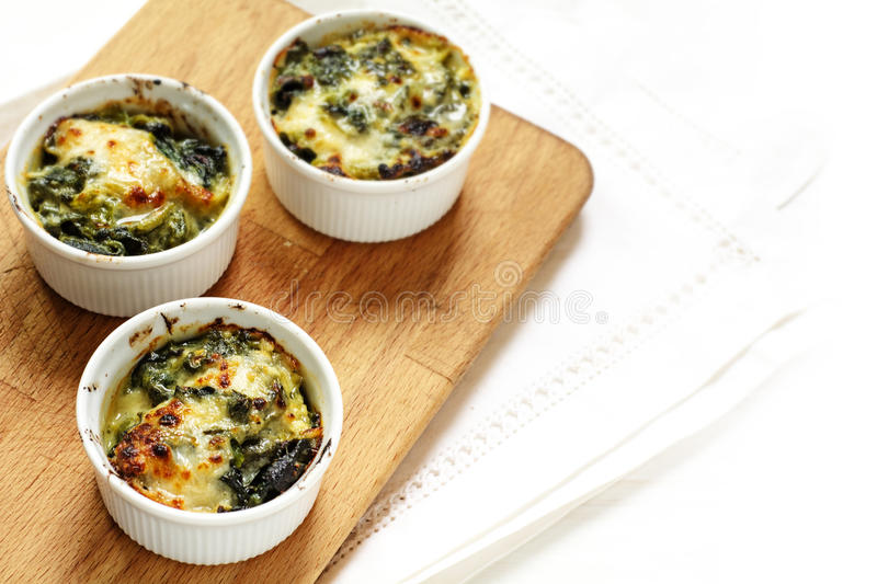 Baked spinach with cheese in three small casserole dishes on a. Baked spinach with cheese crust in three small casserole dishes on a wooden board, white napkin royalty free stock image
