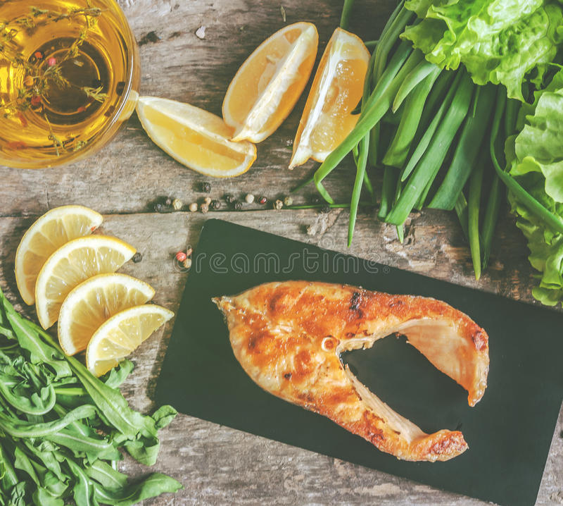 Baked steak trout fish on a stone board, around greens, leaves, royalty free stock photos
