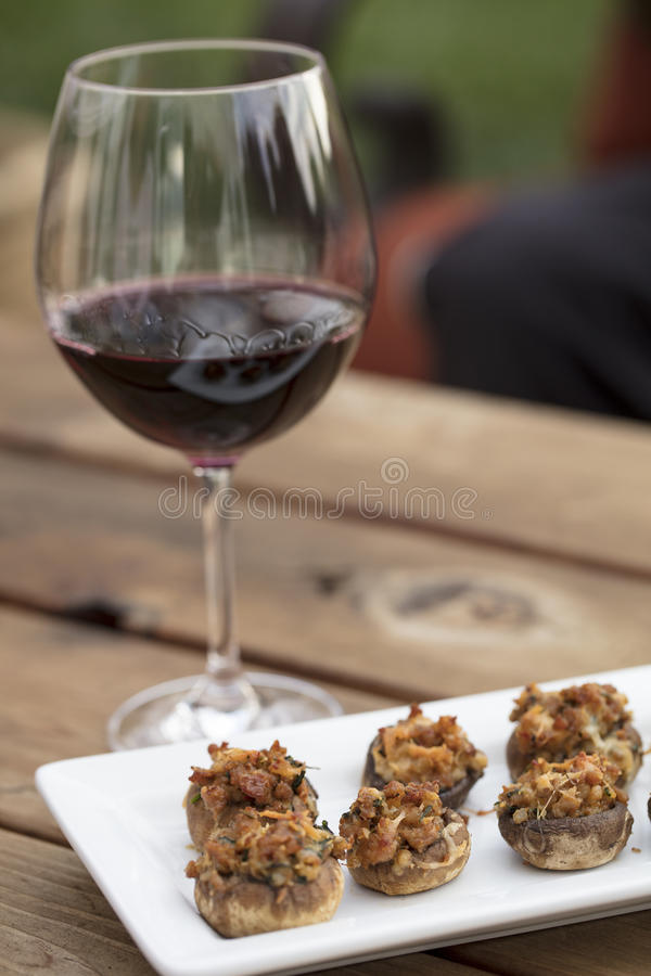 Baked Stuffed Mushrooms with Melted Cheese. Sausage and Cheese baked stuffed mushrooms plated on white ceramic on a wood table and glass of wine royalty free stock photo