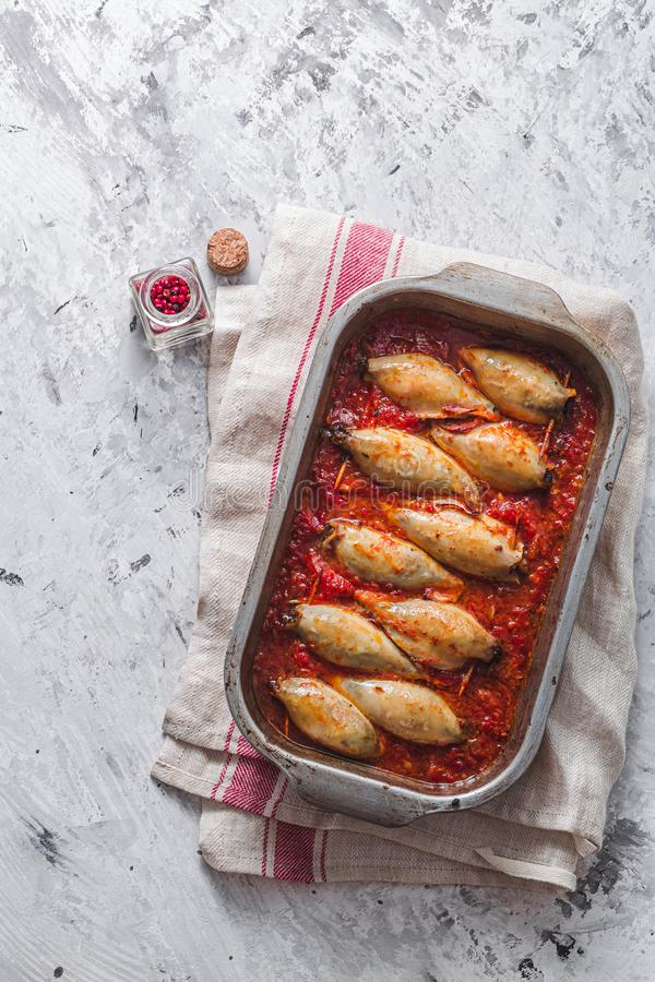 Baked stuffed squid with tomato sauce, copy space stock photos