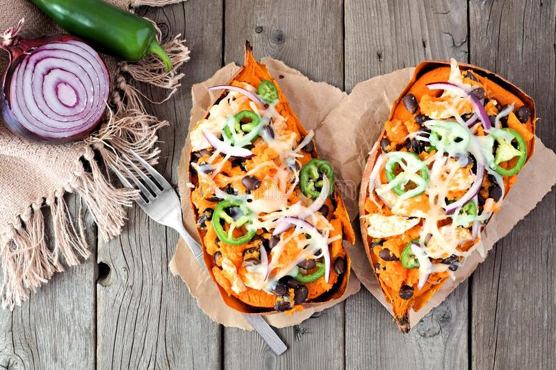 Baked, stuffed sweet potatoes, above view on rustic wood stock photo