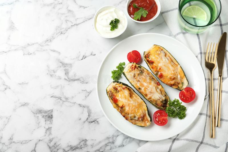 Baked stuffed zucchinis  with sauces on white marble table, flat lay. Space for text stock images