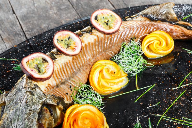 Baked sturgeon fish with rosemary, lemon and passion fruit on plate on wooden background close up. Healthy food. Top view. Russian traditions. Top view stock image