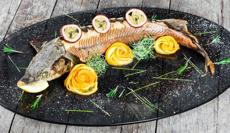 Baked sturgeon fish with rosemary, lemon and passion fruit on plate on wooden background close up. royalty free stock photography