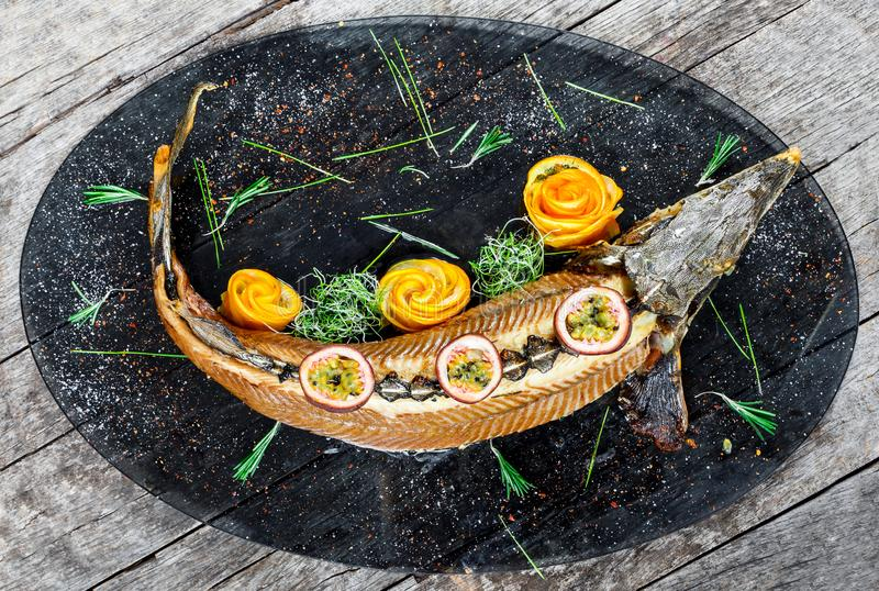 Baked sturgeon fish with rosemary, lemon and passion fruit on plate on wooden background close up. Healthy food. Top view. Russian traditions. Top view royalty free stock image