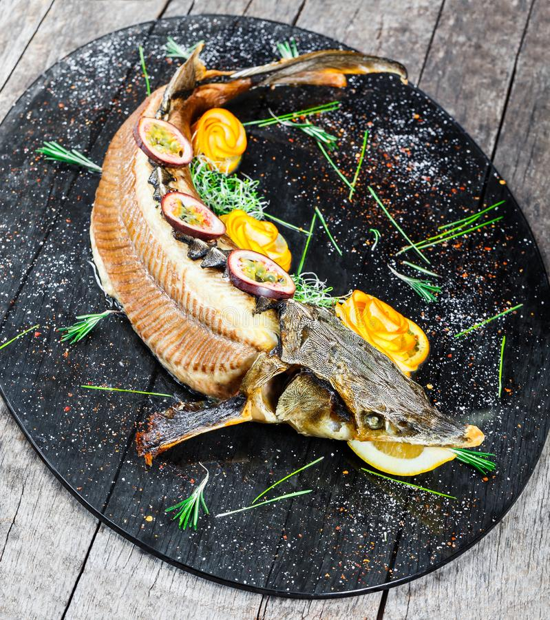 Baked sturgeon fish with rosemary, lemon and passion fruit on plate on wooden background close up. Healthy food. Top view. Russian traditions. Top view stock photos