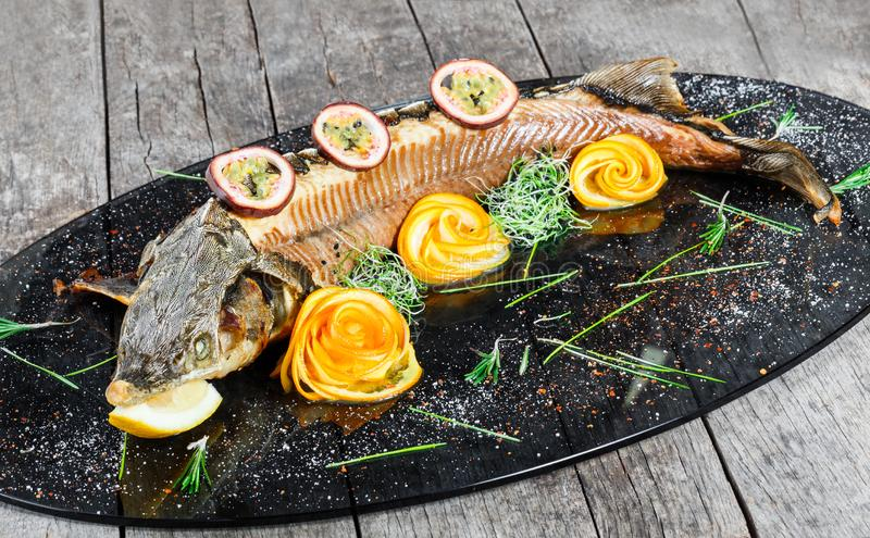 Baked sturgeon fish with rosemary, lemon and passion fruit on plate on wooden background close up. Healthy food. Top view. Russian traditions. Top view stock photo