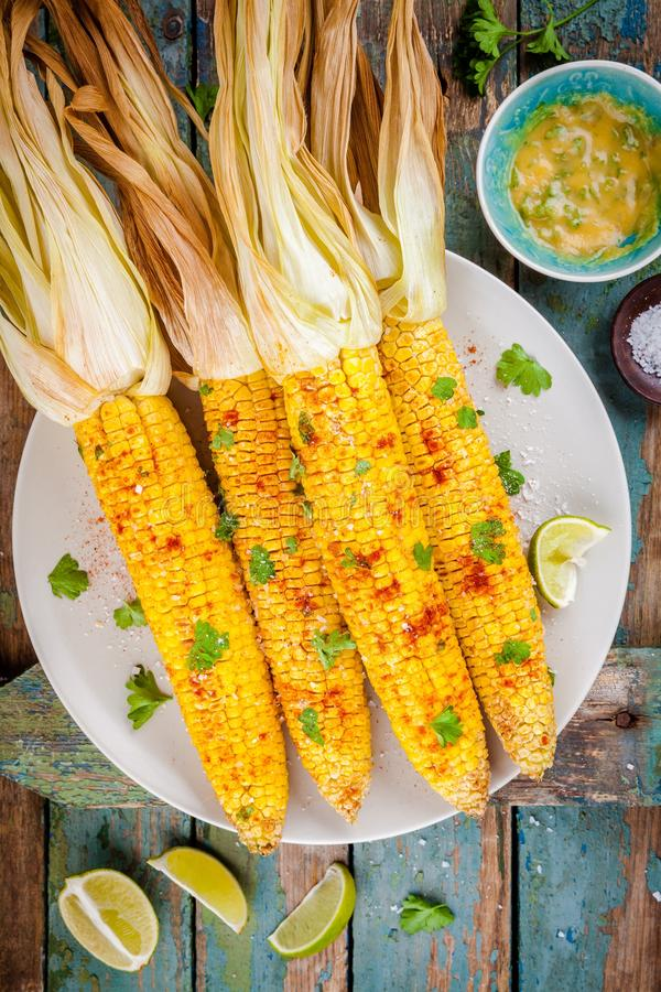 Baked sweet corn cobs with herb butter and lime. On wooden table royalty free stock images