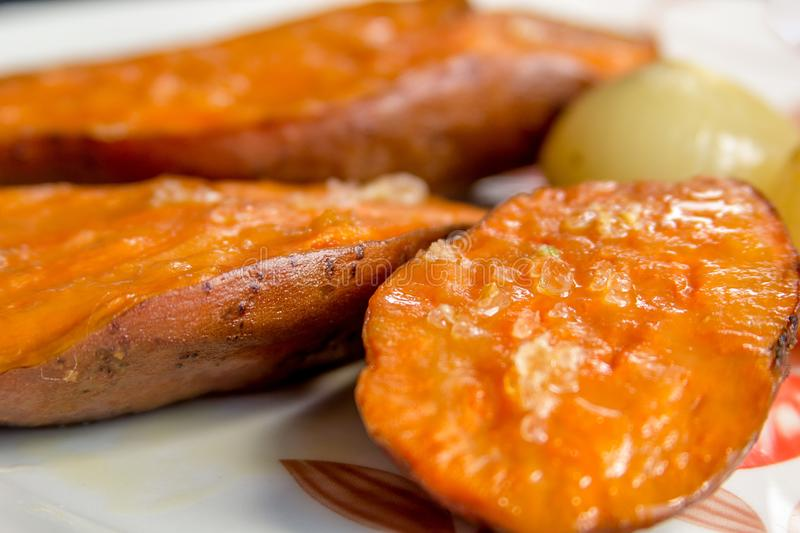 Baked sweet potato with coarse salt. On the top and an onion on the back royalty free stock photography