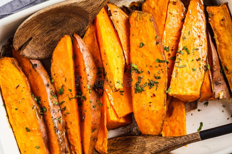 Baked sweet potato slices with spices in oven dish. Healthy vegan food concept royalty free stock image