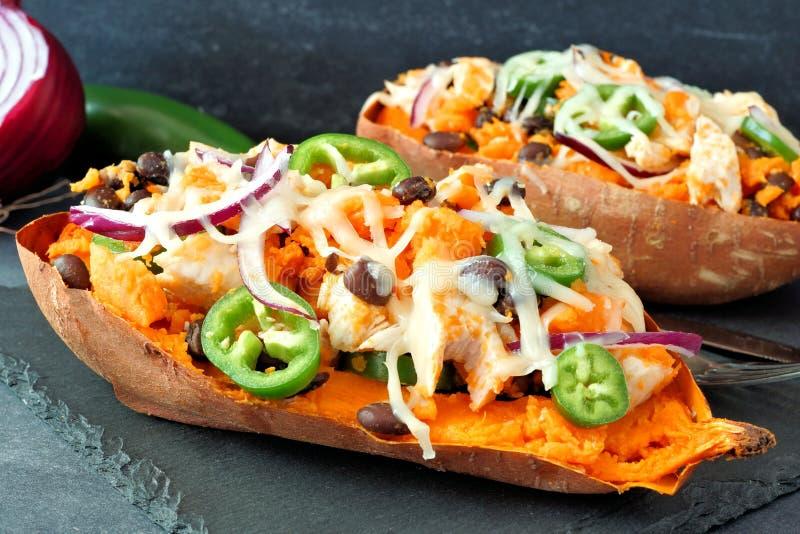 Baked, stuffed sweet potatoes, close up on dark background royalty free stock photo