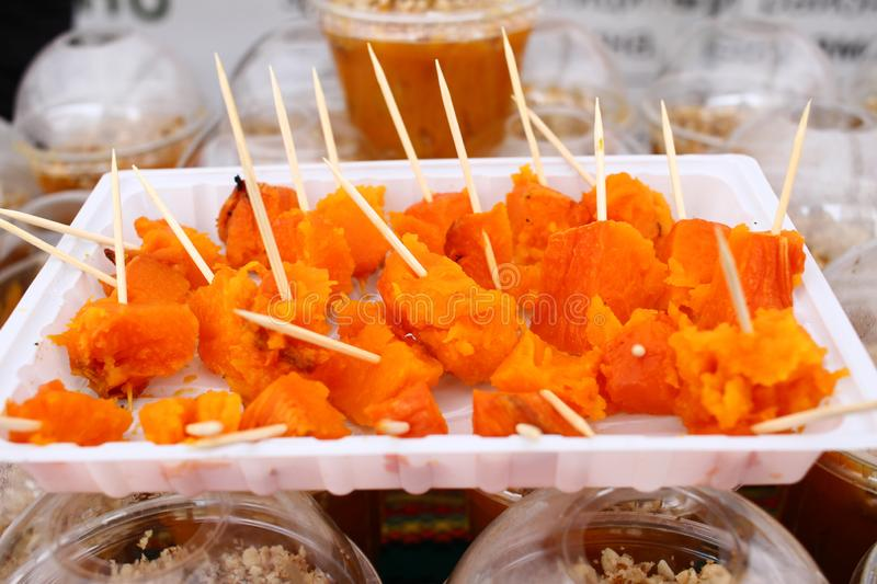 Baked sweet pumpkin bites. Roasted Squash Gourmet pieces on wooden sticks. Vegetables backgrouns pattern. Food wallpaper. Slices o. F baked pumpkin with honey stock image