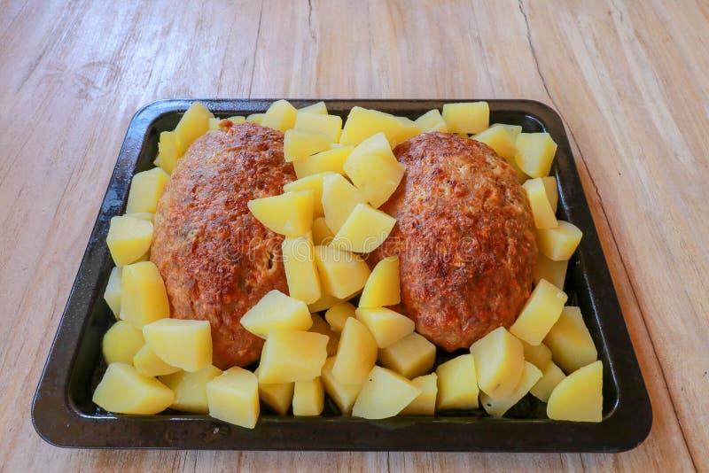 Baked triturou a carne de porco e as batatas em uma bandeja de cozimento preta Alimento colocado na tabela de madeira Fundo com d fotos de stock