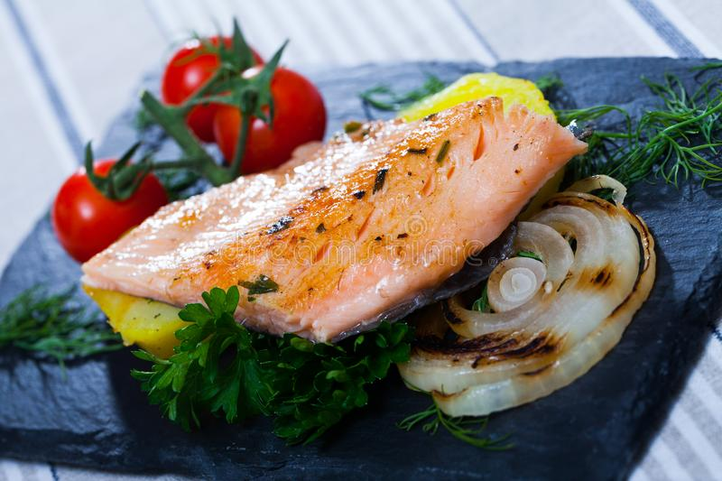 Baked trout fillet with potatoes on black board royalty free stock image