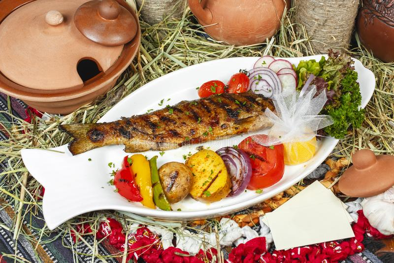 Baked trout fish Georgian recipe with pepper, onion, grilled vegetables and fresh lettuce stock image