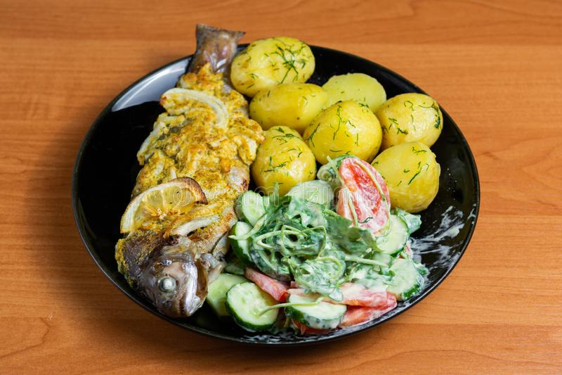 Baked trout with lemon on a plate with arugula, tomato, cucumber salad and young potatoes with dill royalty free stock image