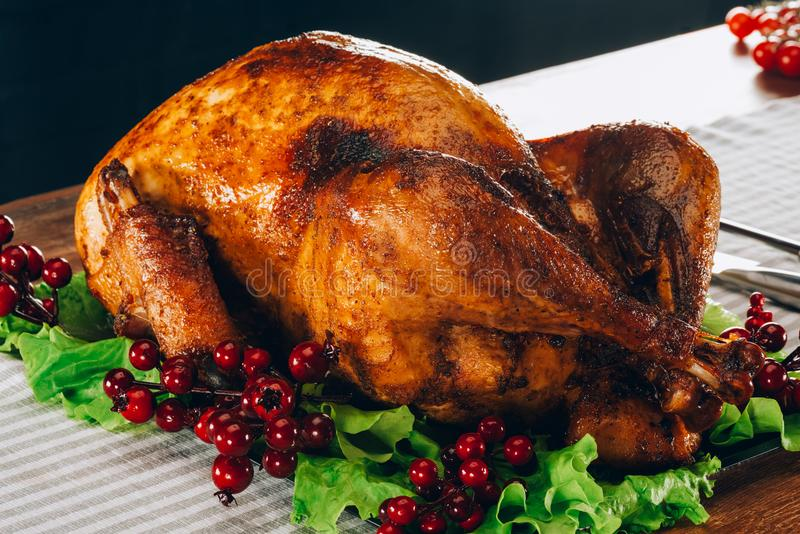 Baked turkey on salad leaves with cranberries. On wooden table stock image