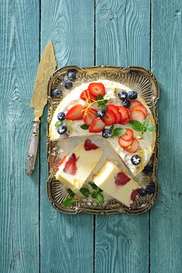 Baked vanilla and lemon cheesecake with fresh strawberries and blueberries stock photography