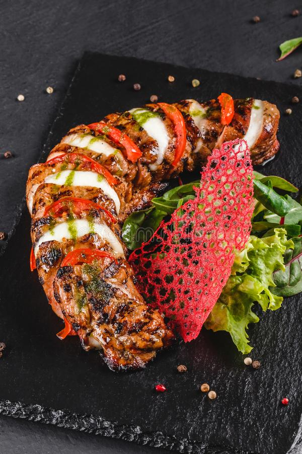 Baked Veal with mozzarella cheese, tomatoes, pesto sauce and green salad on black sbackground. Hot Meat Dishes stock image