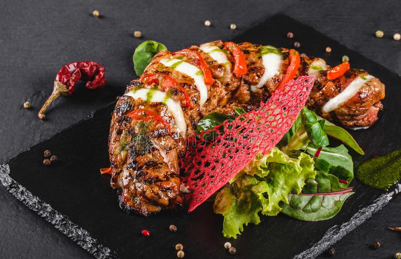 Baked Veal with mozzarella cheese, tomatoes, pesto sauce and green salad on black background. Hot Meat Dishes royalty free stock photos