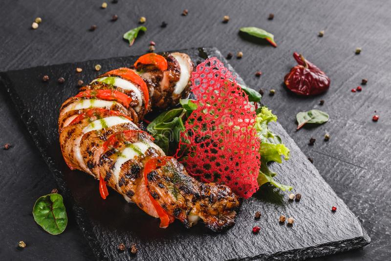 Baked Veal with mozzarella cheese, tomatoes, pesto sauce and green salad on black background. Hot Meat Dishes. Top view, flat lay stock images