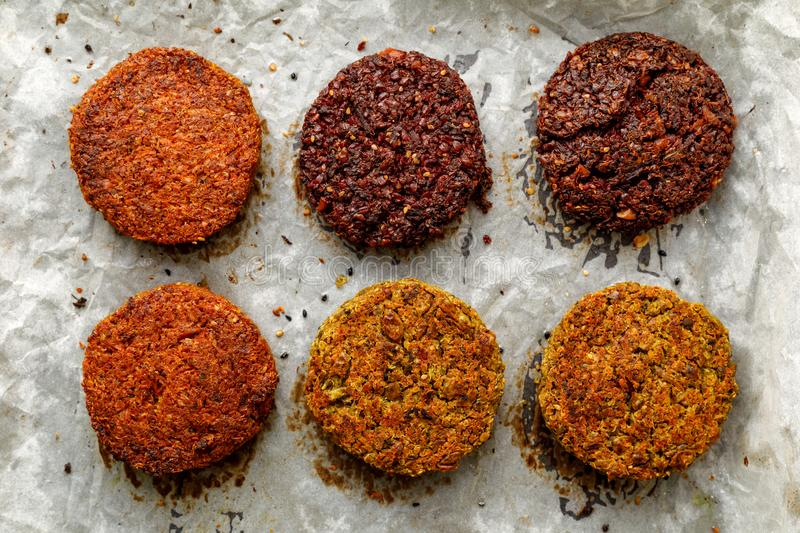 Baked vegan burgers, cutlets made of beetroot, green peas, carrots, groats and herbs on white parchment, top view. stock photo