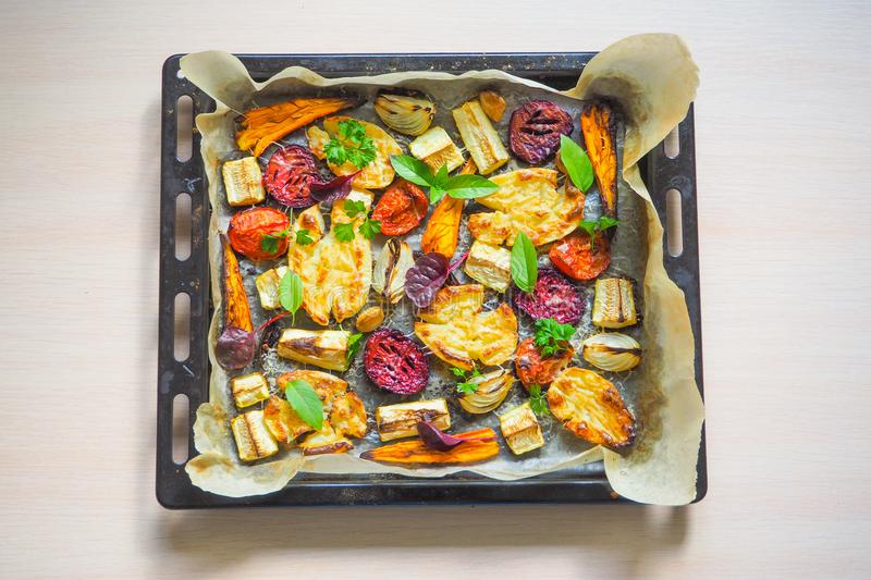 Baked vegetables on an old baking sheet. Top view stock image