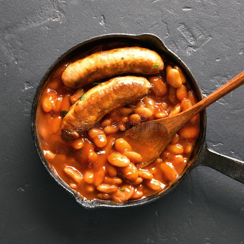 Baked white beans in tomato sauce with sausages royalty free stock photography