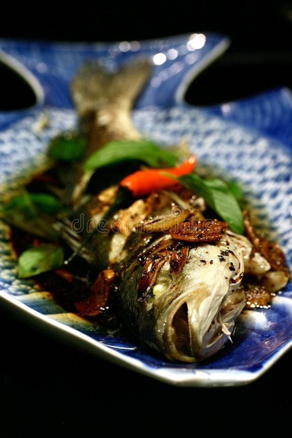 Baked whole seabass. With black sauce, garlic, onion and chilli serve with garnishing of sweet Thai basil stock image