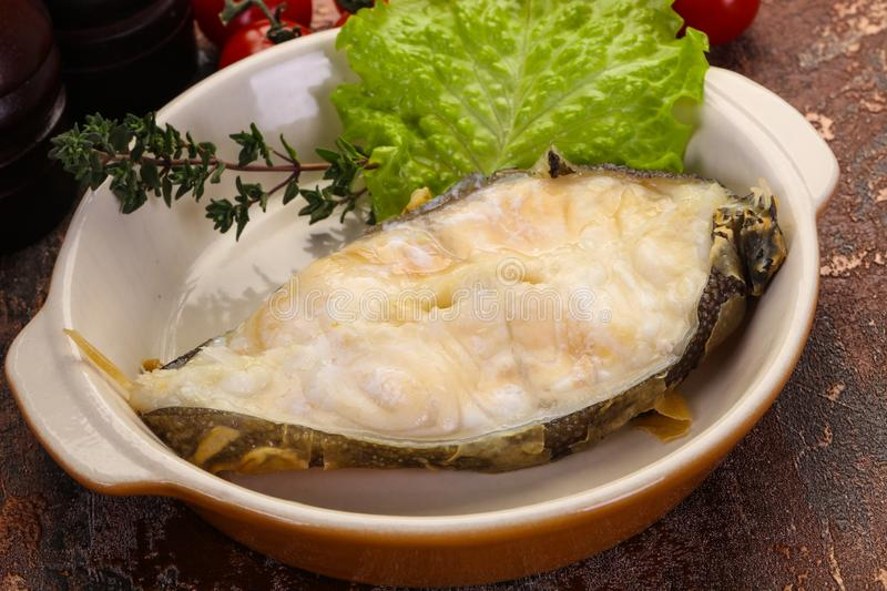 Baked wolffish steak. With salad leaves royalty free stock image