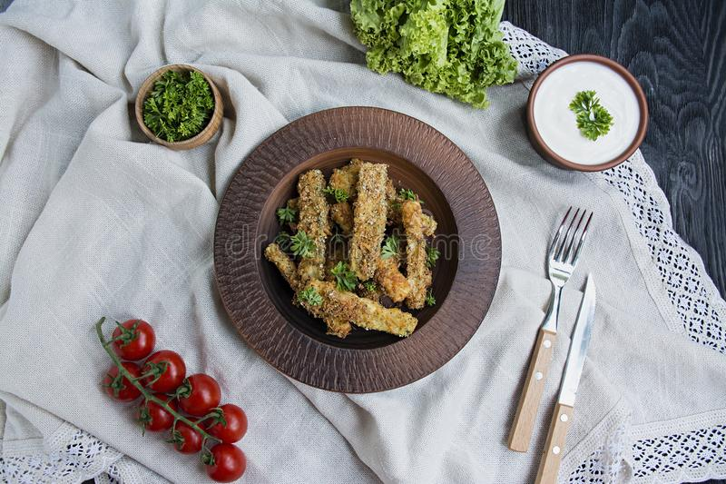 Baked zucchini with cheese and breadcrumbs. Vegan food. Vegetarian cuisine. View from above. Light background stock photography