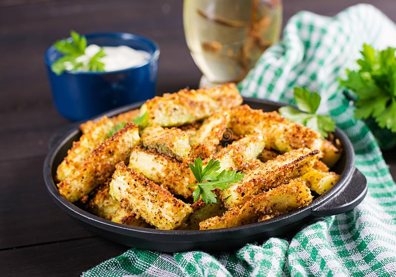 Baked zucchini sticks with cheese and bread crumbs. Vegan food. Vegetarian cuisine stock photography