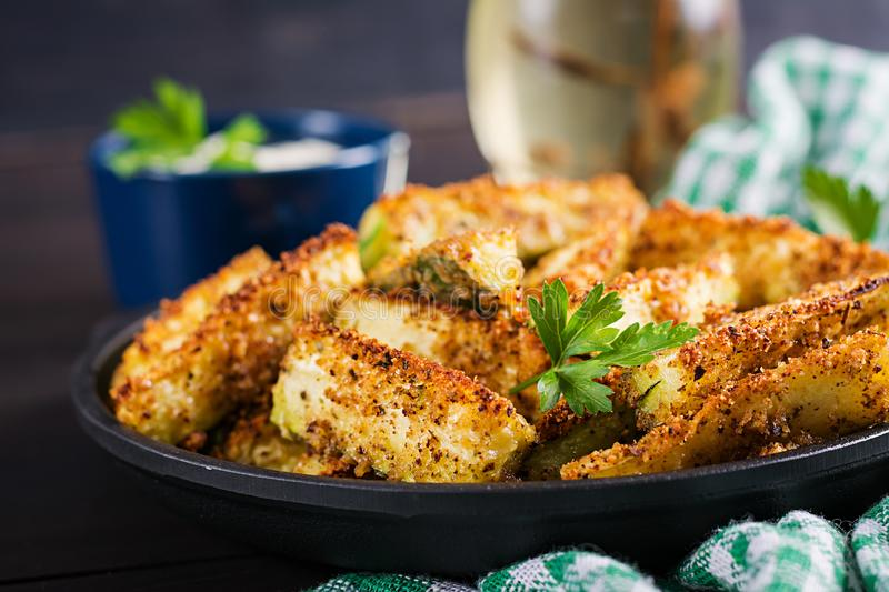 Baked zucchini sticks with cheese and bread crumbs. Vegan food. Vegetarian cuisine stock image