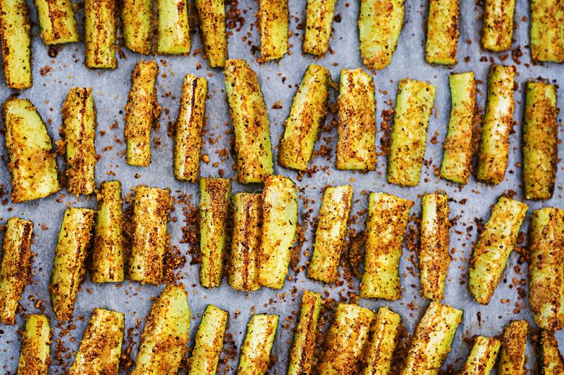 Baked zucchini sticks with cheese and bread crumbs. Vegan food. Vegetarian cuisine. Top view royalty free stock images