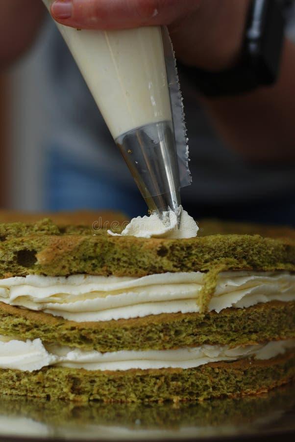 Bakelsepåse med kräm- sättande kräm- garneringar för vit jordgubbe över kakan Grön Matcha kaka som lagar mat Proces Begrepp med m arkivfoto