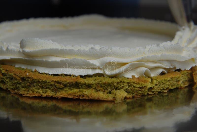 Bakelsepåse med kräm- sättande kräm- garneringar för vit jordgubbe över kakan Matcha kaka som lagar mat Proces Begrepp med mänskl royaltyfri foto