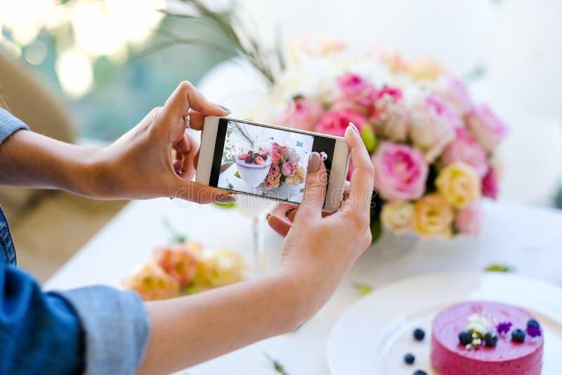 Bakelser för parti för foto för kvinnabloggersmartphone royaltyfri bild