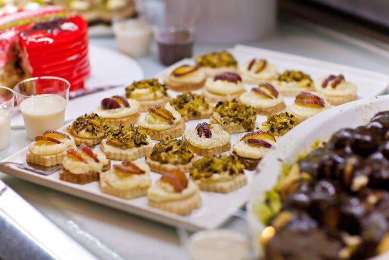 Bakelser med frukt och pistascher på buffétabellen royaltyfri foto