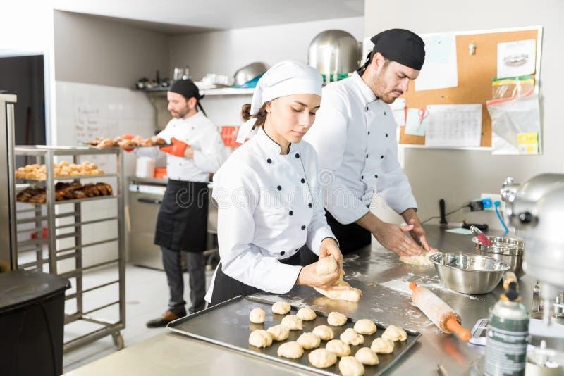 Bakelsetillverkare med deg i kök arkivbilder