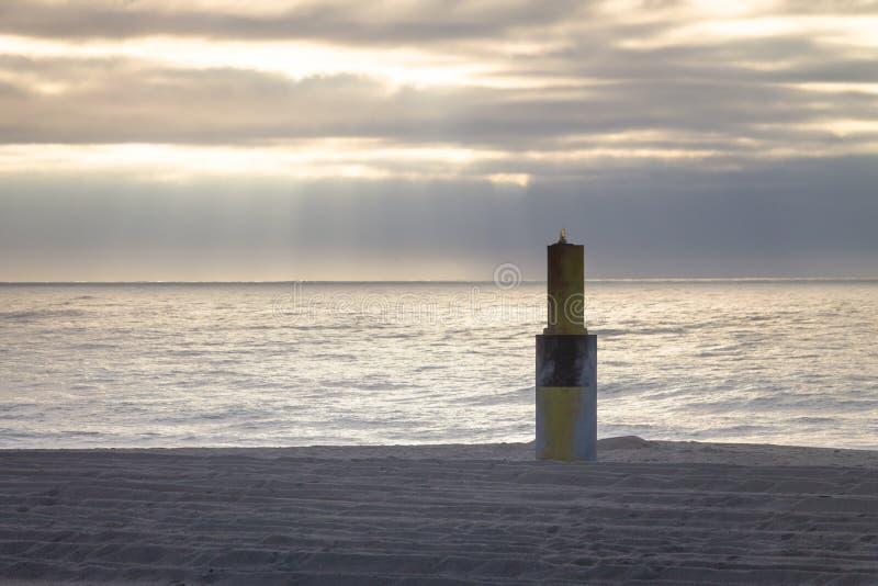Baken in het Zand dichtbij de Oceaan stock foto's