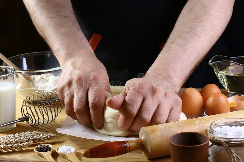 Baker ζυμώνει τα συστατικά συνταγής ψωμιού, πιτσών ή πιτών ζύμης με τα χέρια, τρόφιμα στο επιτραπέζιο υπόβαθρο κουζινών, που λειτ στοκ εικόνες