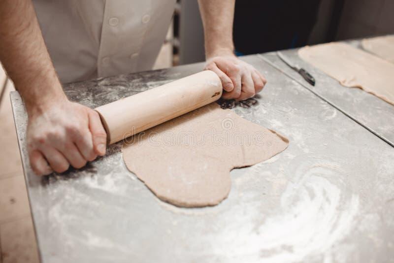 Baker κυλά τη ζύμη στον πίνακα στο αρτοποιείο στοκ φωτογραφία με δικαίωμα ελεύθερης χρήσης